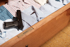 Gun hidden in a drawer full of shirt at home. Clothes royalty free stock images