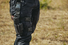 The gun hidden in a holster hanging on a soldier's leg. Stock Photos