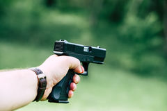 The gun is in his hand. The man is ready to shoot at the target. Royalty Free Stock Images