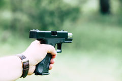 The gun is in his hand. The man is ready to shoot at the target. Stock Images
