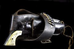 Gun in Holster on Black. An old western six gun revolver isolated against  a black background in the  horizontal format Stock Photo