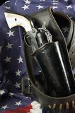 Gun in Holster on Flag. An old western six gun revolver isolated against  a flag background in the  vertical format Royalty Free Stock Photography