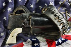 Gun in Holster on Flag. An old western six gun revolver isolated against  a flag background in the  horizontal format Stock Photos