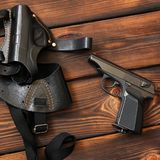 The gun and holster for a handgun on wooden background. Weapon royalty free stock photography