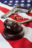 Gun laws. A wooden gavel on an american flag with a gun and bullets in the background, focus on the gavel stock image