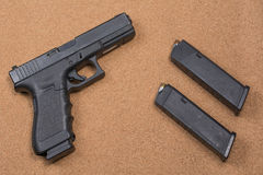 Gun and magazines on background. Gun with two magazines laying on natural colored cork board Stock Photo