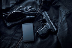 Gun, mobile phone and leather jacket on black background. Criminality concept stock image