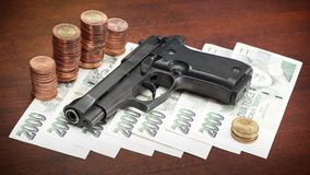 Gun and money. Gun on money symbolising money-related criminality Stock Images