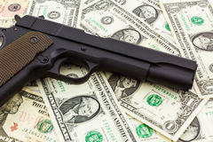 Gun on money background. Stock Images