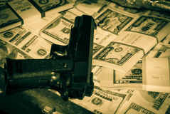 Gun and money. Black gun on the background of packs with money Stock Images