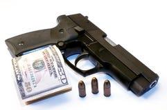 Gun and money. Close up image of 9mm gun, bullets and dollars Royalty Free Stock Photography