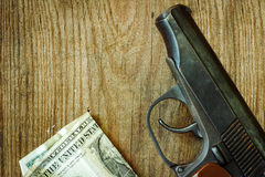 The gun and money on wooden table. Stock Photo