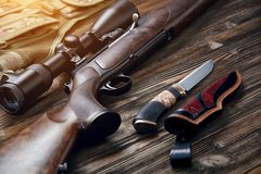 Hunting equipment on old wooden background. A gun with an optical sight, a hunting knife on a wooden background Stock Photos