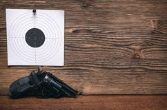 Gun and paper target. Shooting practice. Shooting range. Gun pistol and paper target. Shooting practice. Shooting range background with copy space Royalty Free Stock Images