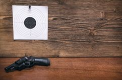 Gun and paper target. Shooting practice. Shooting range. Gun pistol and paper target. Shooting practice. Shooting range background with copy space Royalty Free Stock Photo