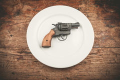 Gun on plate. A revolver lying on a white plate Stock Image