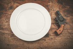 Gun and plate Stock Images