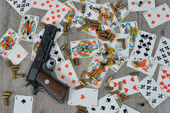 Gun with playing cards. Gun with somes bullets on the table with playing cards Stock Photos