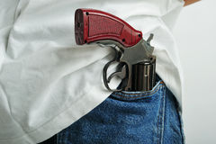 Gun in pocket. Close up of a pistol holded in jeans back pocket Royalty Free Stock Photography