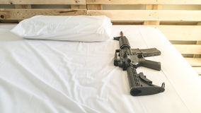 Gun Put on a comfortable mattress and pillow white . Royalty Free Stock Image