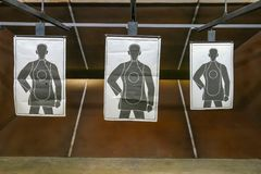 Gun Range three targets close shot. Indoor Gun Range with three paper targets no people one target hit royalty free stock images