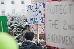 Gun rights rally Montpelier Vermont. A Vermont man attending a pro-second amendment rally holds a sign while listening to a speaker during the Guns Across Royalty Free Stock Photo