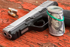Gun with a roll of 100 dollar banknotes. And two bullets lying on a grungy wooden surface with red peeling paint conceptual of crime, robbery, coercion, bribe Stock Photo