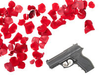 Gun between the rose petas Royalty Free Stock Image