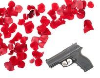 Gun between the rose petas Royalty Free Stock Image