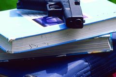 Gun on school books. Depicting school gun violence a school backpack grip bag has a Glock 40mm semi-auto or semi auto handgun gun in his bag on top of school stock photo