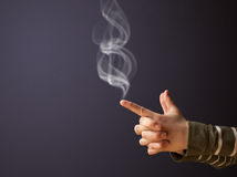 Gun shaped woman hand with smoke Stock Image