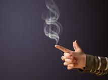 Gun shaped woman hand with smoke. Gun shaped woman hand with white smoke stock image