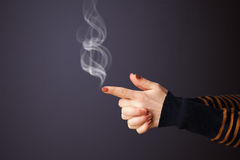 Gun shaped young woman. Hand with smoke royalty free stock photography