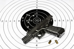 Gun and shooting target. A gun, bullet casings and shooting target with bullet holes Stock Photos