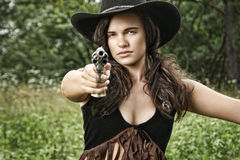 Gun Shots - Miss Sherif. Fashion portrait of model in western gear with guns and horse - fantasy scenario Royalty Free Stock Image