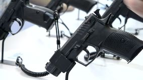 Gun at the show. Person taking a gun in hand close-up. Firearms gun submachine sniper rifle large-caliber weapons close-up stock footage