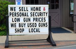 Gun Sign. Sign outside of a small sporting goods store in Northwest, New Jersey advertising guns for protection.(Small sign in window shows that the store also Royalty Free Stock Image