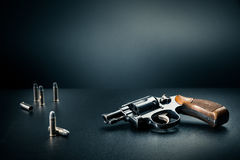 Gun sitting on a table with bullet shells / dramatic lighting. Gun sitting on a table with bullet shells Royalty Free Stock Images