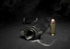 Gun and smoke. Smoking gun with bullet on the black background royalty free stock image