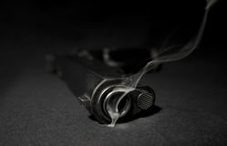 Gun and smoke. Closeup image of Smoking gun on black background