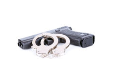 Gun and steel handcuffs Stock Photo