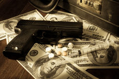 Gun,syringe and pills on dollar bills. Stock Images