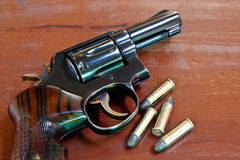 The gun on the table. Revolver with bullets on brown wooden table Stock Photos
