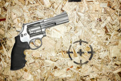 Gun and target on wooden background.  Royalty Free Stock Image