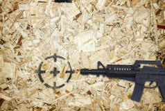 Gun and target on wooden background Royalty Free Stock Photo