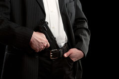 Gun in trousers. Isolated on black Royalty Free Stock Photography