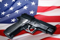 Gun on USA flag. Handgun lying on American flag Royalty Free Stock Photography