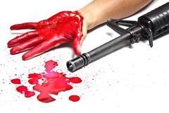 Gun violence. A M16 rifle with bloody hands and blood drops stock image