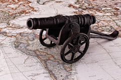 Gun, war and map. Miniature cannon on the map in a retro style, vintage Royalty Free Stock Photos