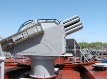 Gun on a warship. Near a pier in port Royalty Free Stock Images